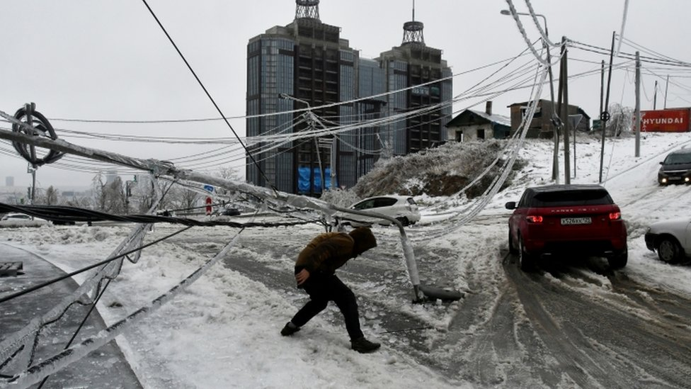 A man walks under a damaged power pole covered with ice after freezing rain in the far eastern city of Vladivostok, Russia