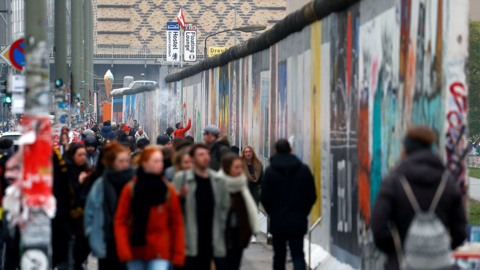 Tourists walk in front of sections at the East Side Gallery, the largest remaining part of the former Berlin Wall, as Germany marks the 28th anniversary of the fall of the wall in Berlin, Germany, November 9, 2017