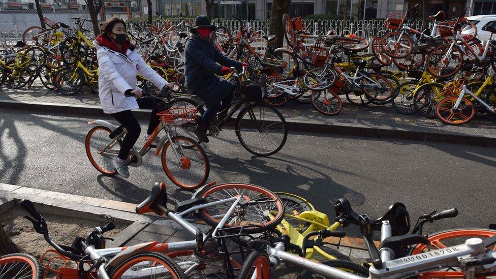 Gente manejando bicis en Pekín en 2018.