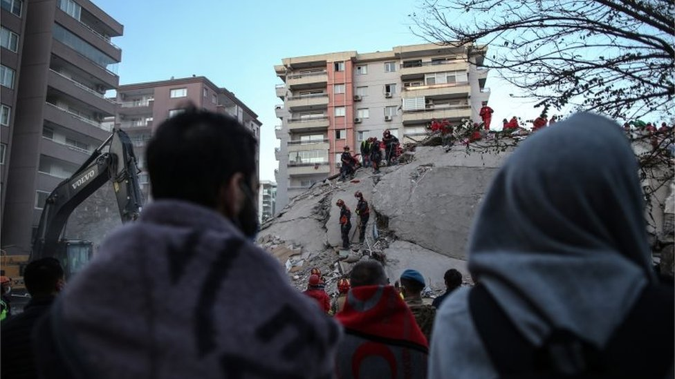People stay near a collapsed building and wait for news from their relatives believed to be trapped under collapsed buildings after a 7.0 magnitude earthquake in the Aegean Sea; at Bayrakli district in Izmir, Turkey, 31 October 2020