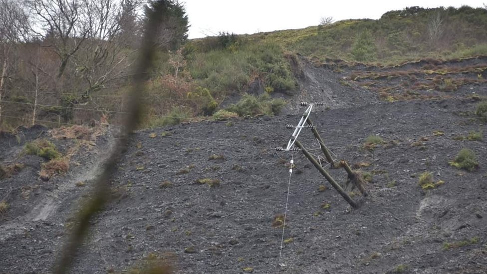A telegraph pole on its side in a landslide