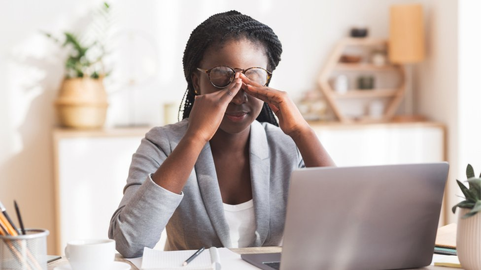 Woman at laptop looking stressed and rubbing her eyes under her glasses