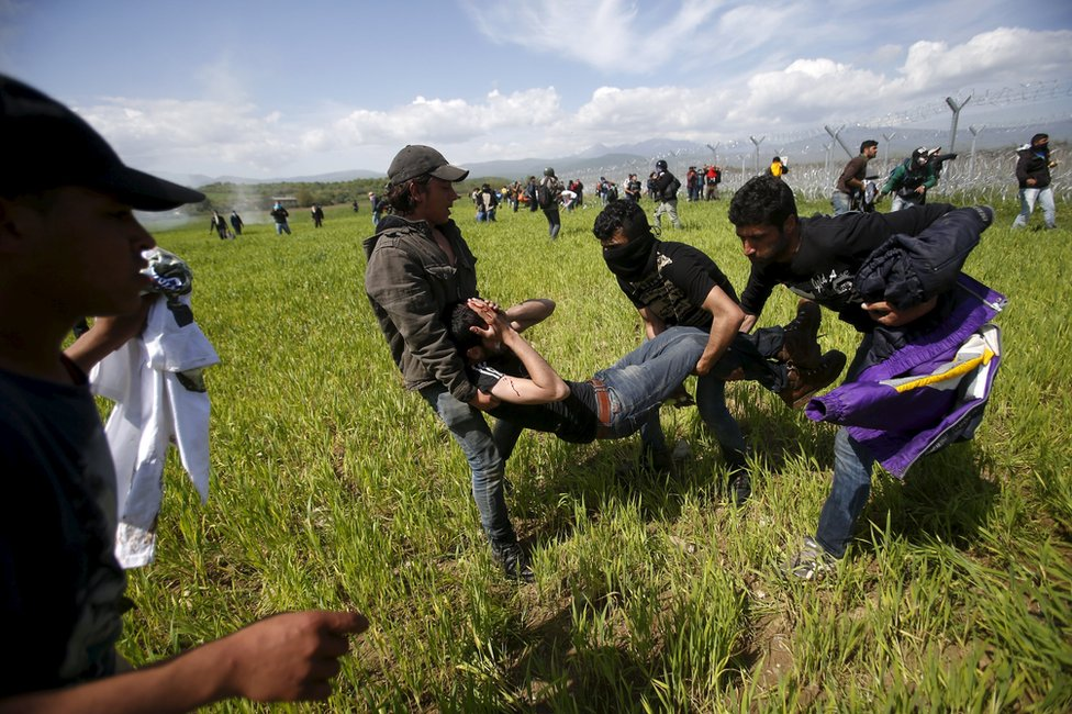 Migrants flee tear gas thrown by Macedonian police on the Greek border at Idomeni, 10 April