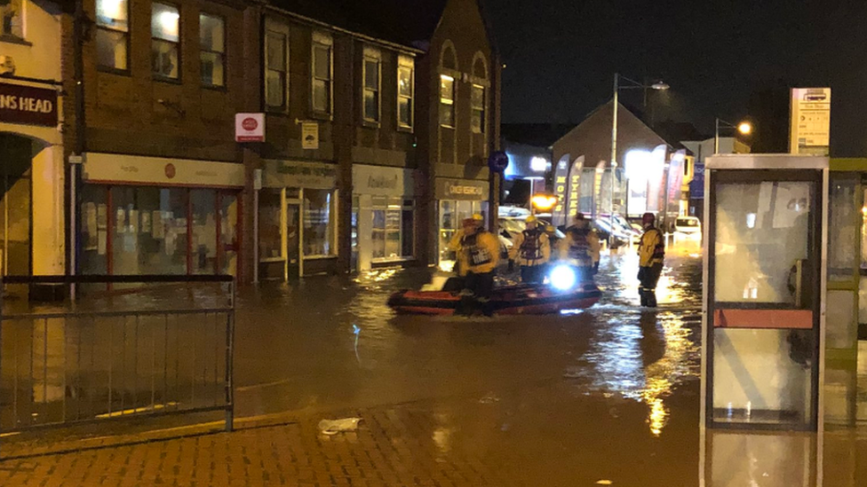 Firefighters on boat in flooded town centre