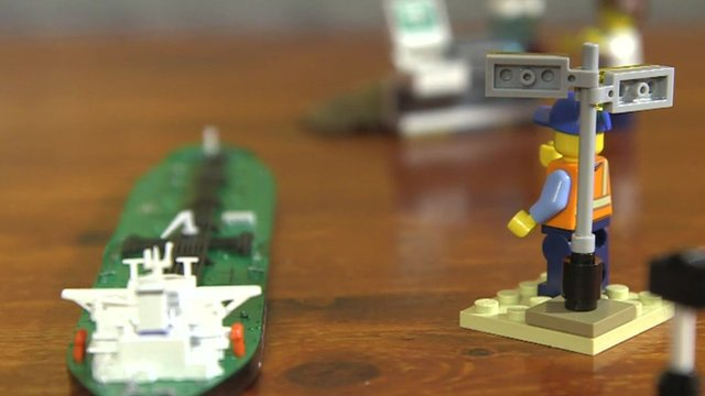 Lego man directing an oil tanker