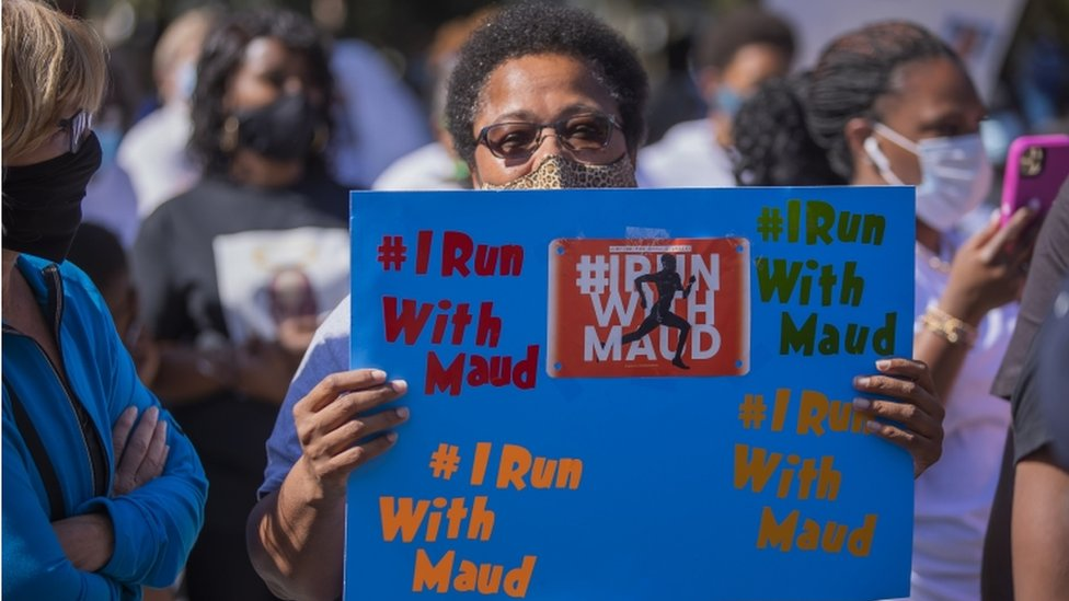 A woman holds an 'I stand with Maud sign at a protest after the shooting death of Ahmaud Arbery