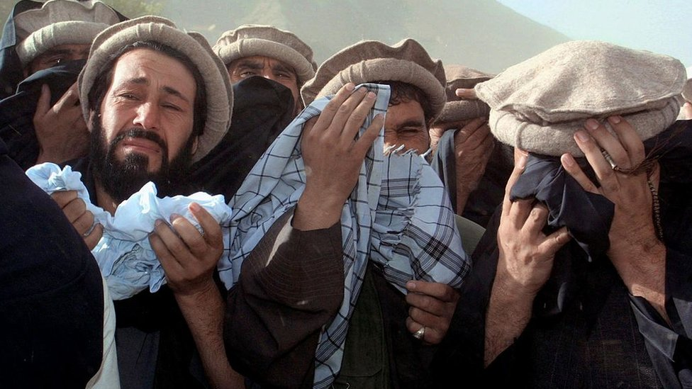 Afghan men crying at a funeral ceremony