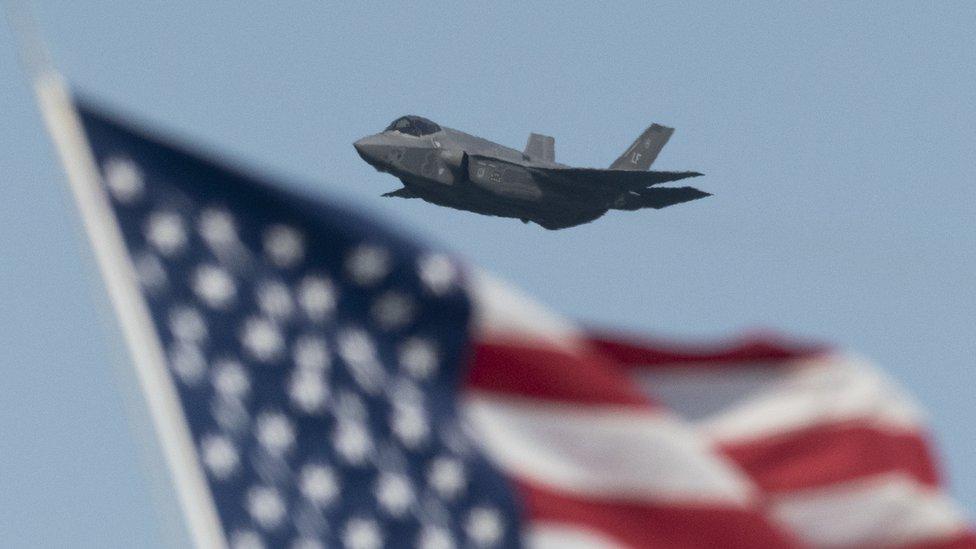 Un avión F35 volando con una bandera de Estados Unidos a la vista