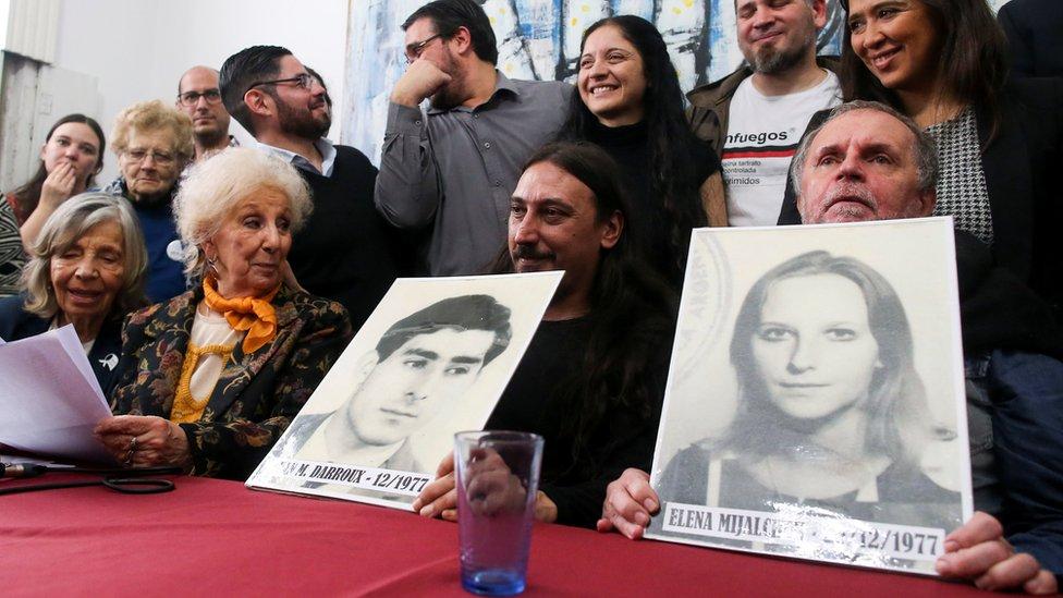 """Javier Matías, su tío Roberto y Estela de Carlotto, presidenta de Abuelas de Plaza de Mayo, exponen fotografías de los progenitores del """"nieto 130""""."""