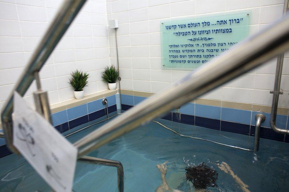 Una mujer judía se sumerge en las aguas de un mikveh, en Jerusalén. 17 de abril de 2019. (Foto de Heidi Levine para la BBC).
