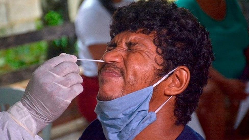 Homem faz careta enquanto profissional de saúde introduz swab em seu nariz para fazer teste de covid-19