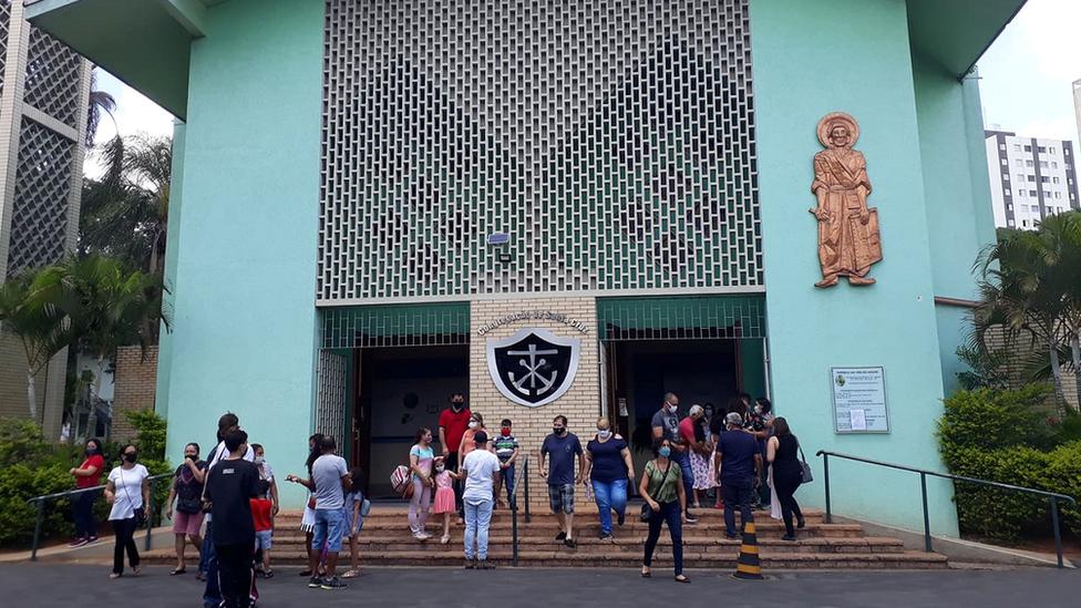 Pessoas reunidas em frente a igreja