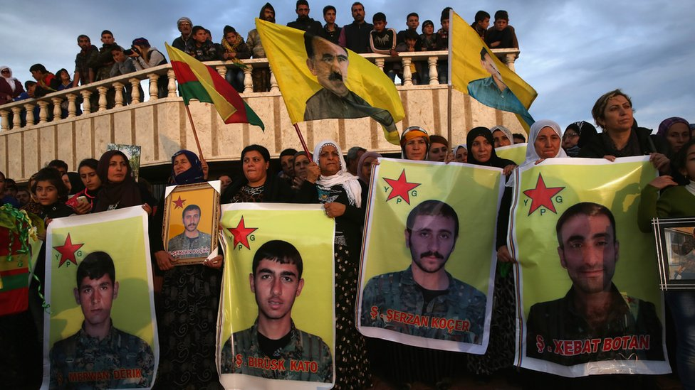 Family members and comrades attend the funeral of eight members of the Popular Protection Units (YPG) in Derek, Syria (8 November 2015). One flag in the background shows PKK founder Abdullah Ocalan