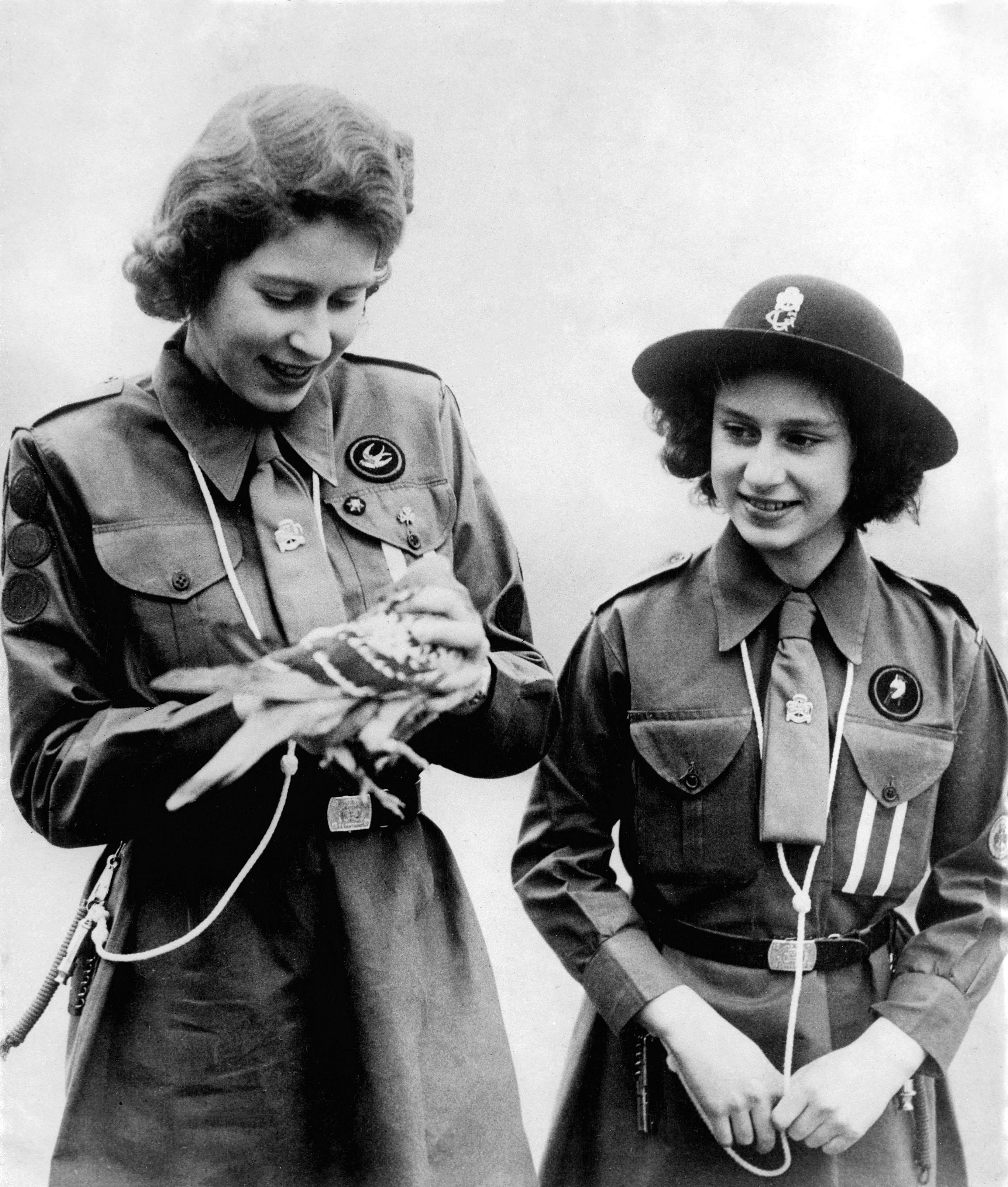 La reina Isabel II, cuando aún era princesa, mostrándole a su hermana Margaret una de las palomas mensajeras.