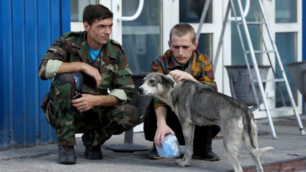 Guardias de Chernóbil con un perro callejero en 2017.
