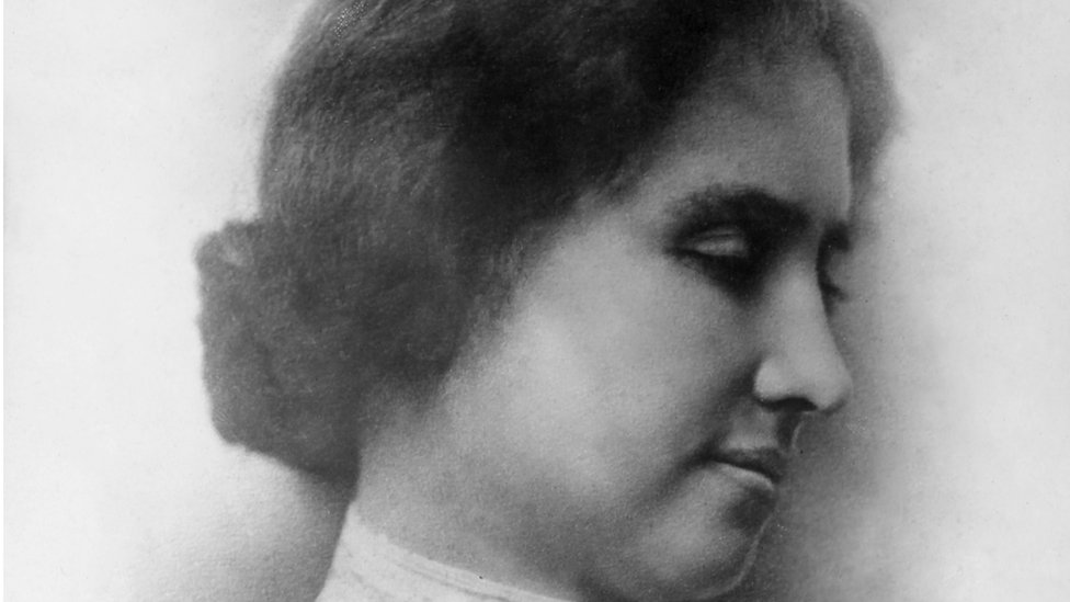 A black and white photo of Helen Keller's side profile. She has brown hair in a low bun and her eyes are downcast
