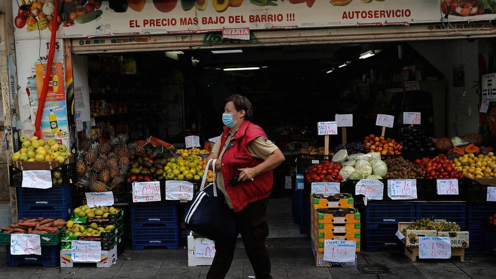 Masked shopper leaves a grocery store in Madrid on 18 September 2020