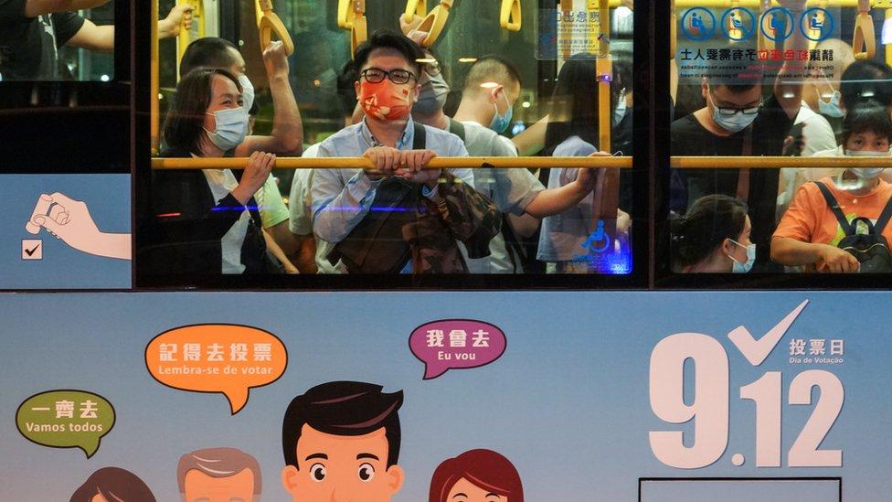 澳門孫逸仙大馬路一輛巴士上站立的乘客看著窗外景色(中新社照片10/9/2021)