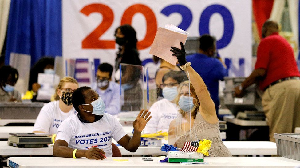 An election worker passes paper to another worker over a plastic screen