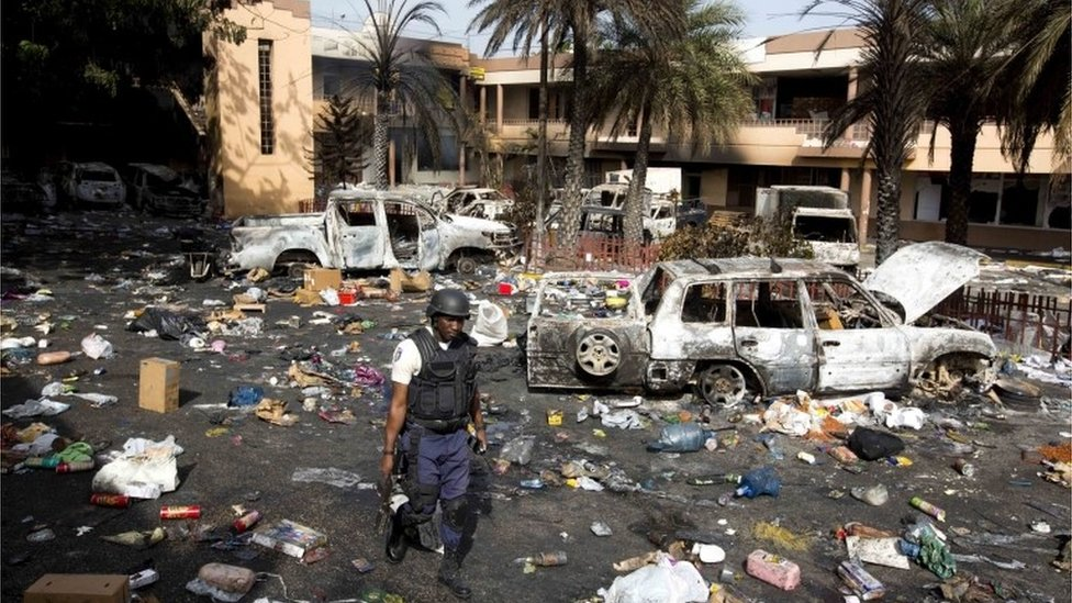 A police officer walks through the parking lot of the Delimart supermarket complex, where vehicles sit charred and looted merchandise lies scattered after two days of protests against a planned hike in fuel prices in Port-au-Prince, Haiti, Sunday, July 8, 2018