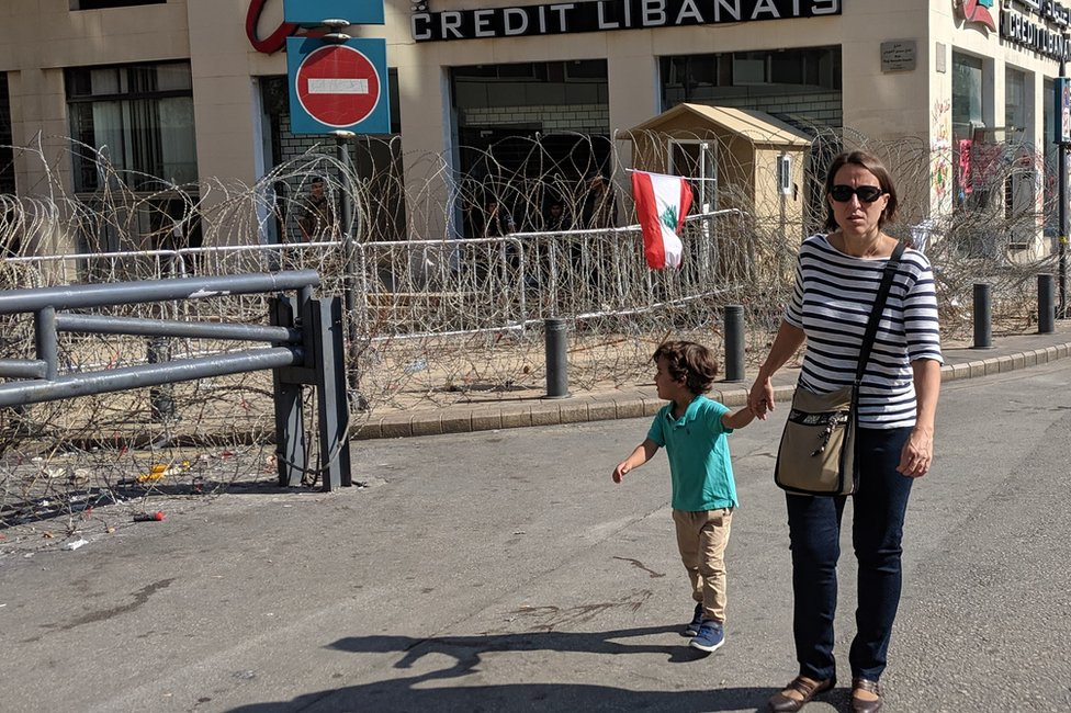 A woman and a child walk past a closed bank in Beirut, Lebanon (4 November 2019)