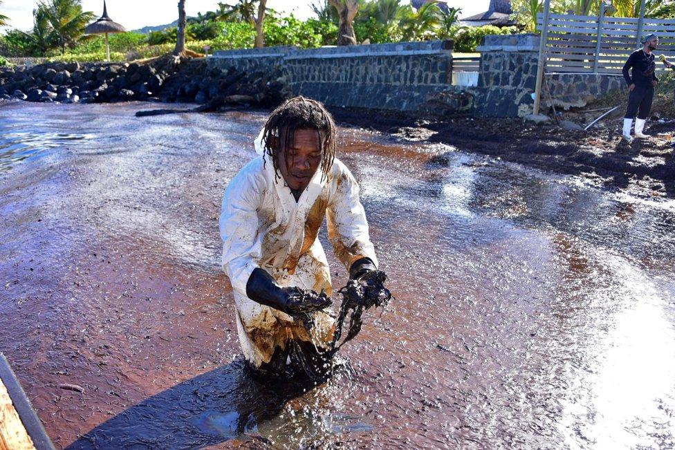 A volunteer stands in leaked oil