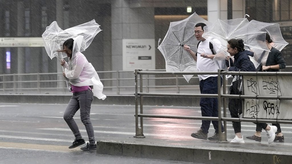 Pedestrians in Tokyo struggle with umbrellas in the wind and rain