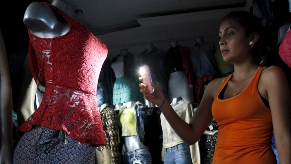 A customer uses her phone's light to look at a dress at a store during a power cut in San Cristobal, in the state of Tachira, Venezuela, April 25, 2016