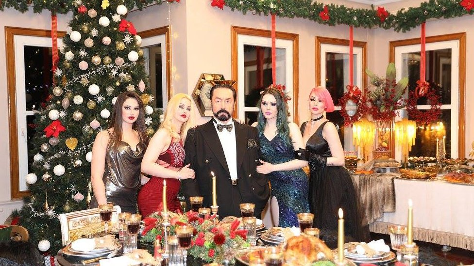 Adnan Oktar stands in a room decorated for Christmas, surrounded by four women on his arms with varying dyed hair colours