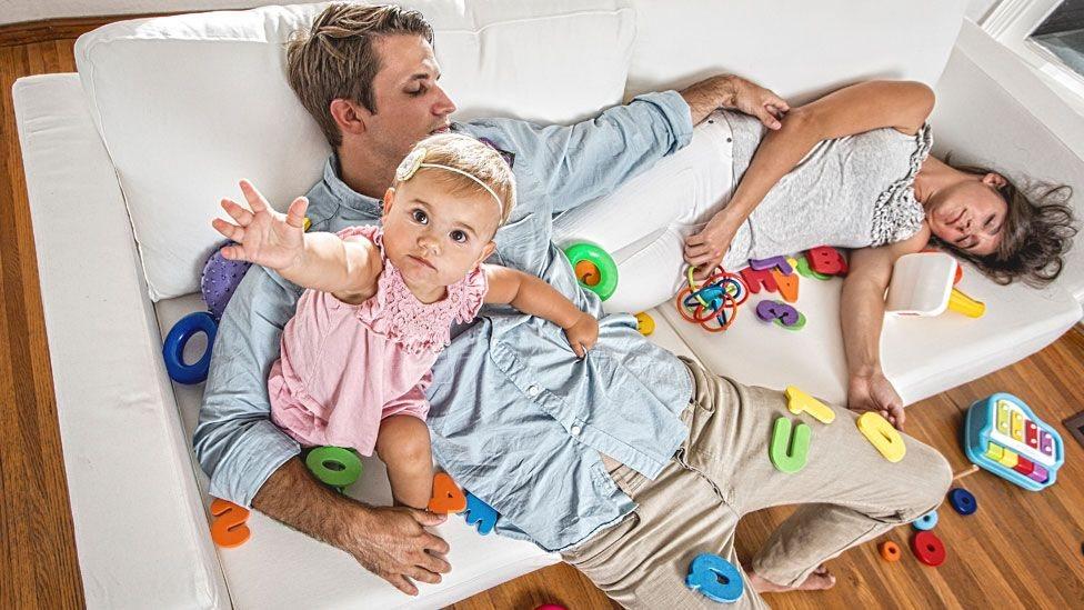 Dos padres echados en un sofá con una bebé