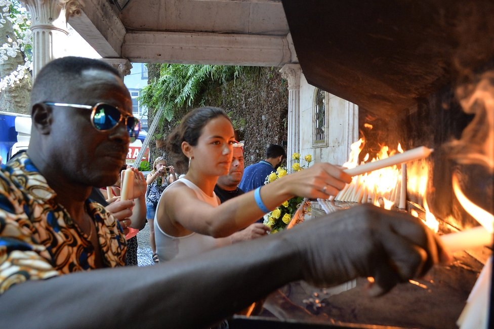People light candles at the area affected by a tree fall that killed 13 people in Funchal, 15 August