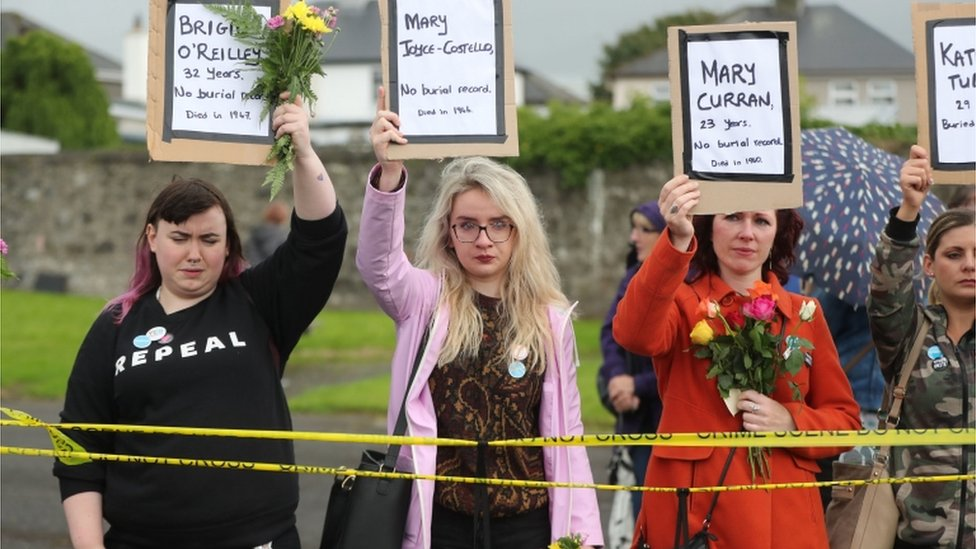 Women hold up placards of the names of babies buried at Tuam