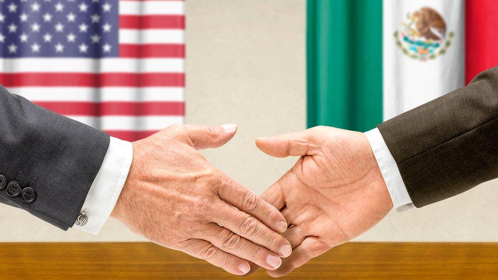 Dos manos estrechándose con las banderas de Estados Unidos y México de fondo.