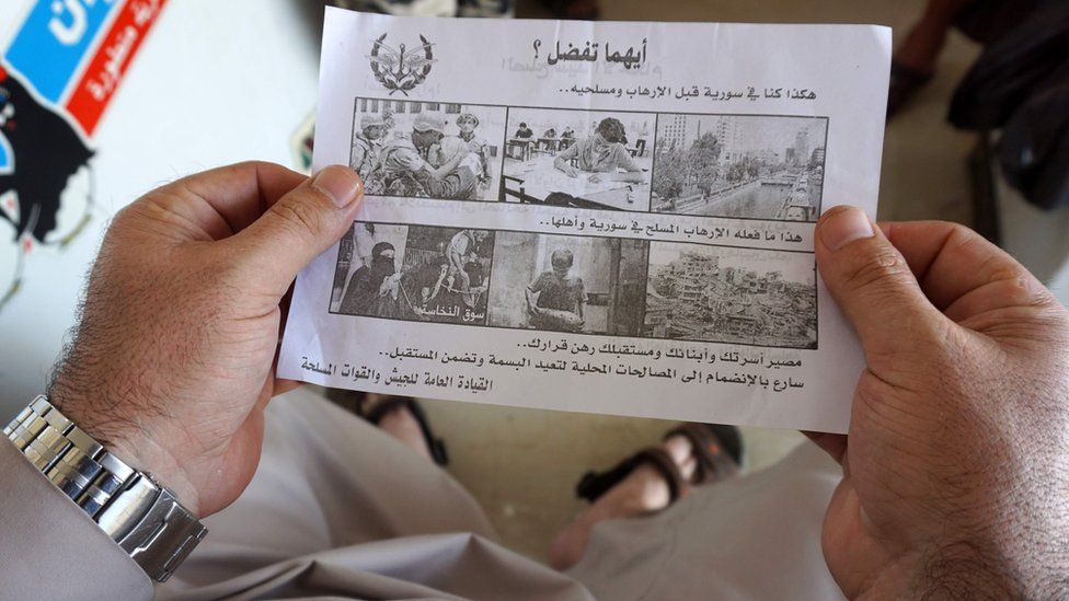 A Syrian man holds a leaflet dropped by the Syrian military over rebel-held Idlib province. It says: