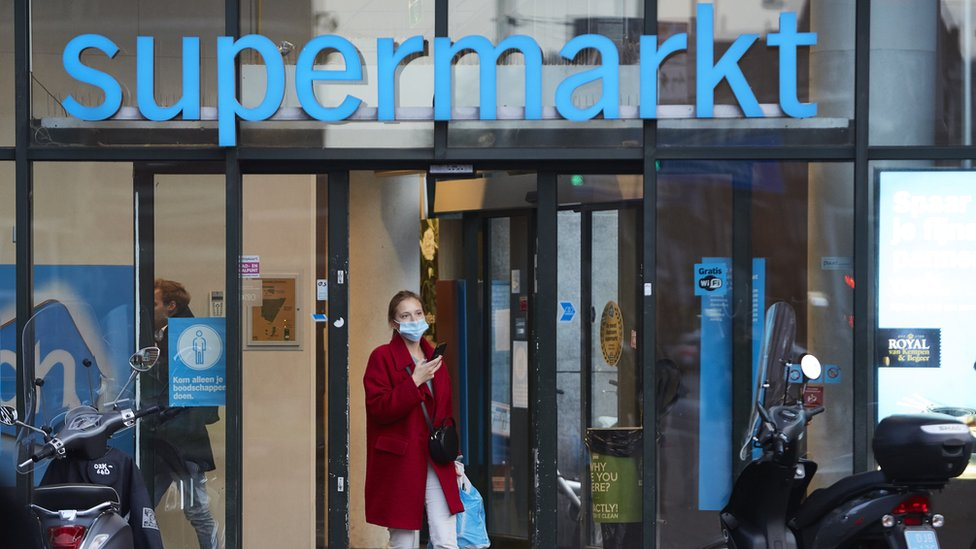 A woman walks out a supermarket wearing a mask on October 14, 2020 in Amsterdam