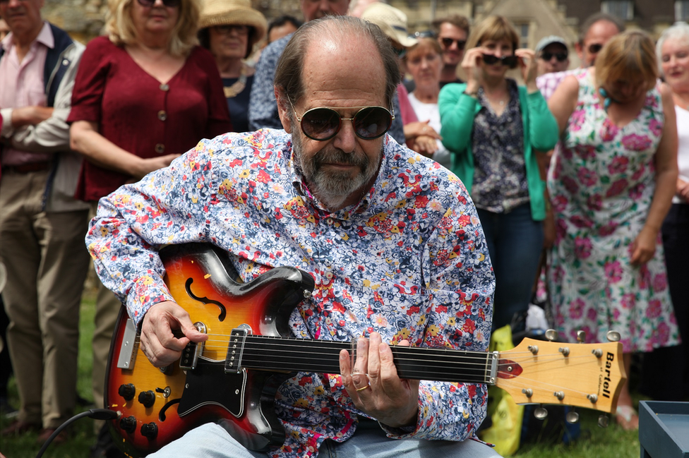 Musician Ray plays the guitar