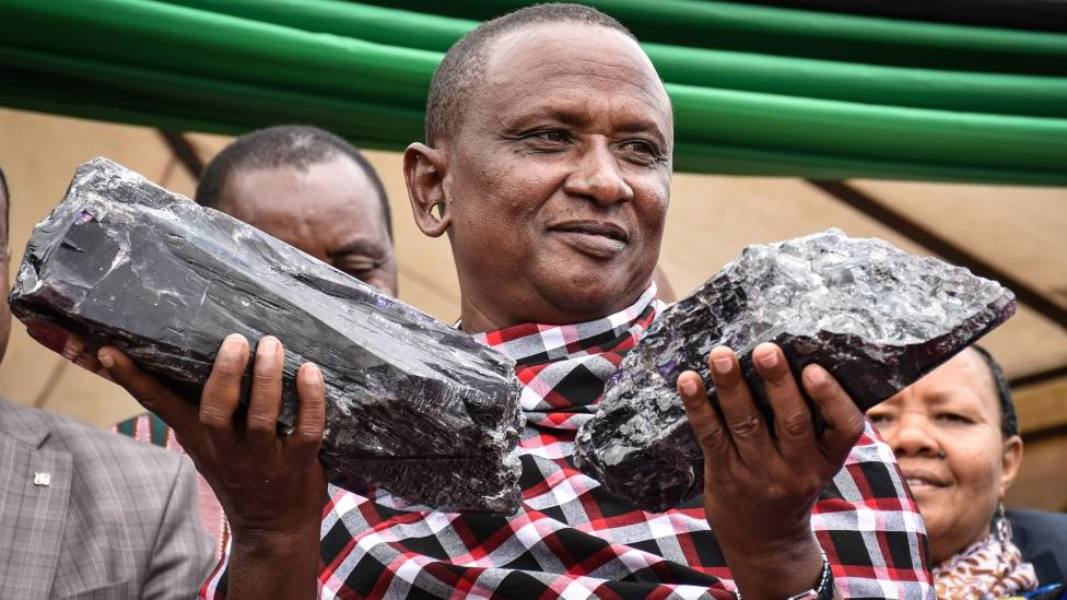 Tanzanian small-scale miner Saniniu Kuryan Laizer poses with two of the biggest of the country's precious gemstones, Tanzanite, as a millionaire during the ceremony for his historical discovery in Manyara, northern Tanzania 24 June, 2020.