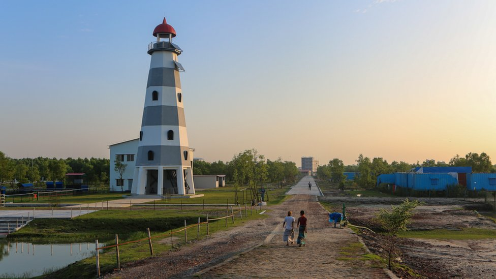 Bathed in evening sun, construction workers walk past the island's lighthouse
