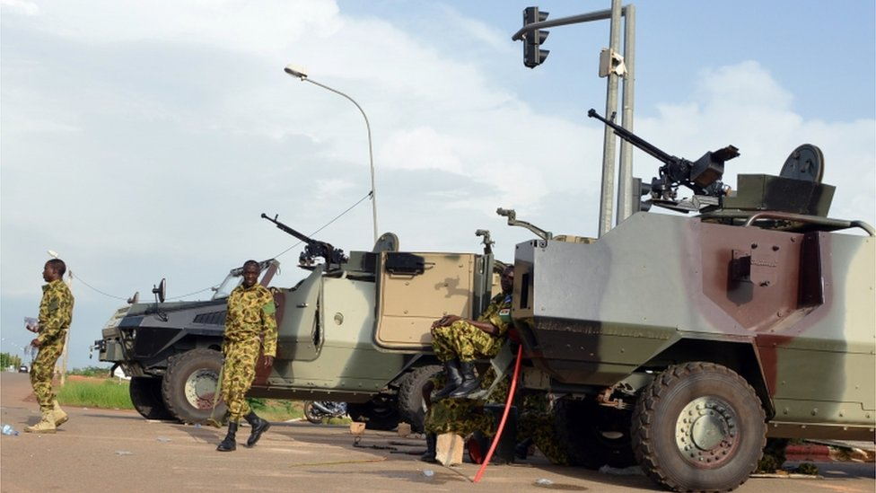 Troops stand next to vehicles on September 17, 2015 outside the presidential palace in Ouagadougou