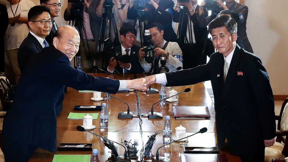 South Korean Park Kyung-seo (L) head of the Korean Red Cross, shakes hands with Pak Yong-il (R) vice chairman of the Committee for the Peaceful Reunification