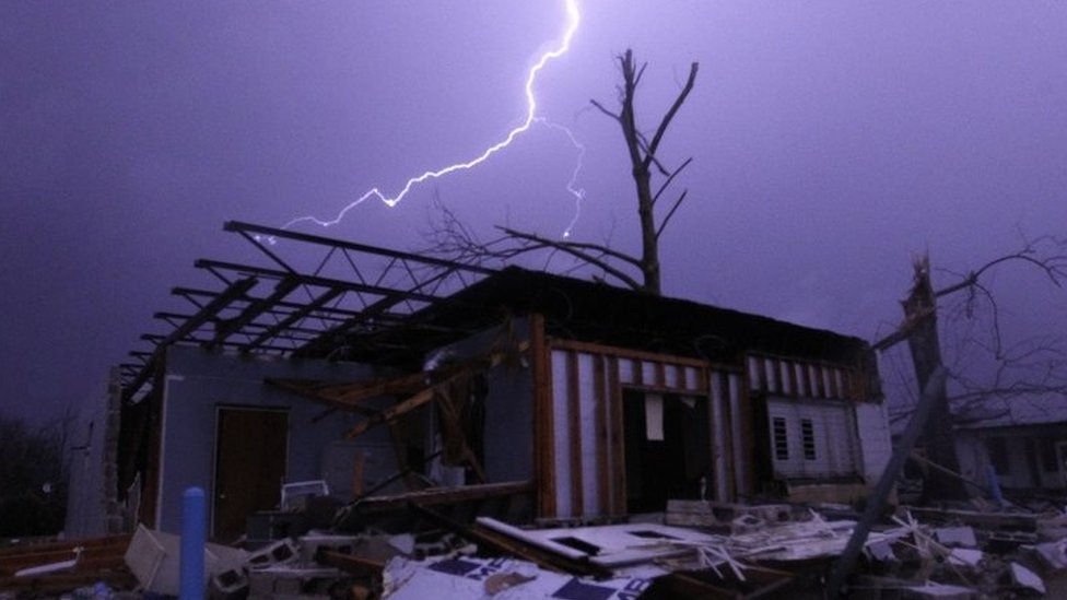 Lightning illuminates a house after a tornado touched down Birmingham, Alabama. Photo: 25 December 2015