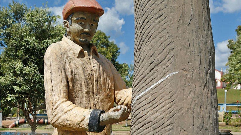 Una escultura en la plaza central muestra el impulsor del proyecto: el preciado caucho del Amazonas.