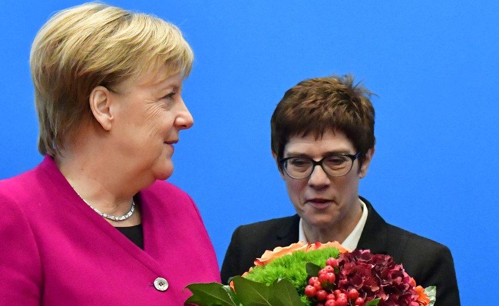 Nemački kancelar i lider Hrišćansko-demokratske unije Angela Merkel prima cveće od generalnog sekretara stranke Anegret Kramp-Karenbauer u oktobru 2018.