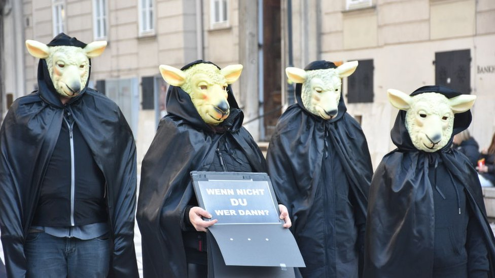 Manifestantes con máscaras de corderos protestan la nueva ley del uso obligatorio de FFP2
