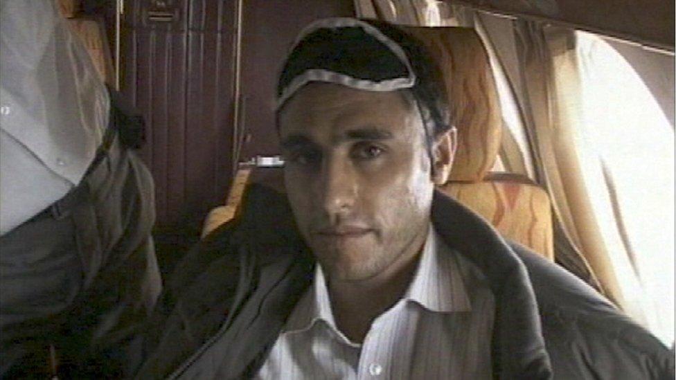 صورة نشرها التلفزيون الإيراني الرسمي تظهر زعيم المتمردين السني عبد الملك ريغي تحت حراسة مسلحة بعد اعتقاله. في 23 فبراير/شباط 2010