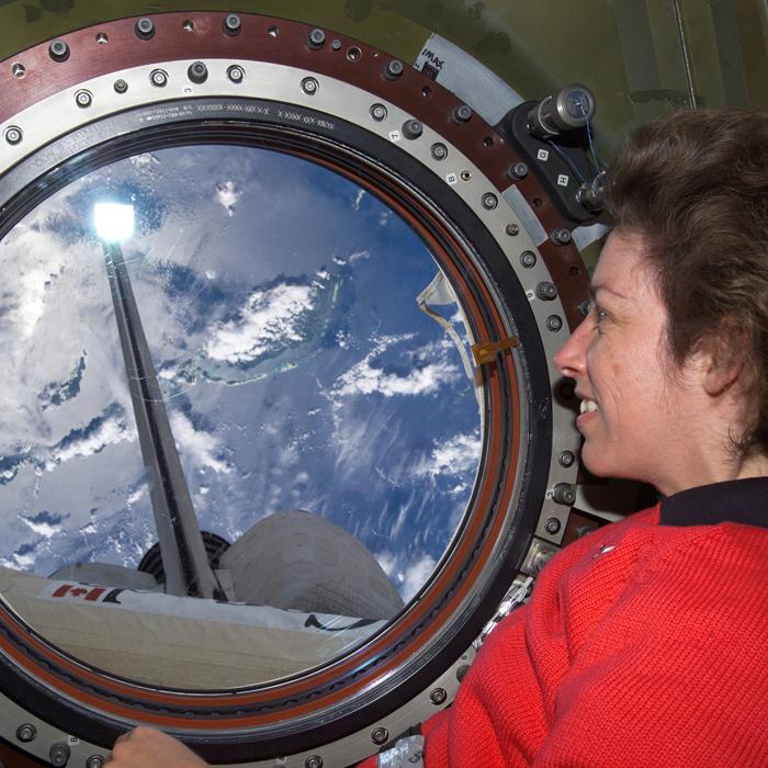 Ellen Ochoa mira a la Tierra desde una ventana de la Estación Espacial Internacional.