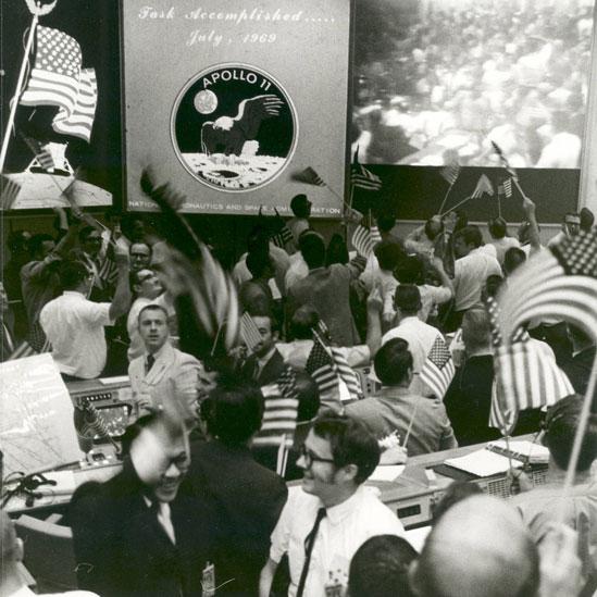 Controladores de vuelo en el centro de control de Apolo 11 celebrando con banderas de Estados Unidos