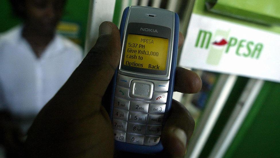 A man sending money via M-Pesa, in Nairobi