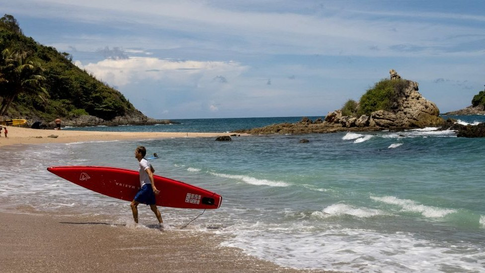 A man carrying his paddle board out of the water on a beach in Phuket