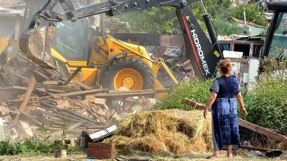 A woman looking on as heavy machines are used by Bulgarian authorities to demolish 50 illegally built homes in the Roma neighbourhood of Varna, 21 August 2015
